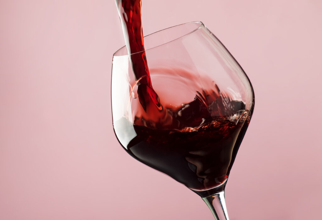 French dry red wine, pours into glass, trendy pink background, space for text, selective focus
